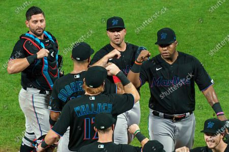 Miami Marlins' Jesus Aguilar, right, celebrates a win with teammates following a baseball game against the Philadelphia Phillies in Philadelphia. Marlins CEO Derek Jeter blames the team's coronavirus outbreak on a collective false sense of security that made players lax about social distancing and wearing masks. Infected were 21 members of the team's traveling party, including at least 18 players
