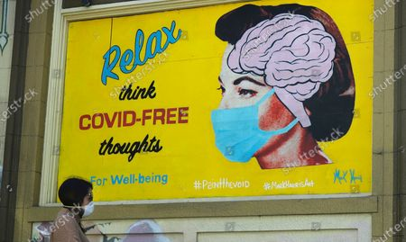 "A woman wears a face mask while walking under a sign that reads ""Relax think COVID free thoughts"" during the coronavirus outbreak in San Francisco, . Gov. Gavin Newsom is cautiously optimistic that California is getting a grip on a resurgence of the coronavirus. But he warned Monday, Aug. 3, 2020, that the state is a long way from reopening some of the businesses it shuttered for a second time last month when new cases, hospitalizations and deaths began surging. The seven-day average and rate of positive tests are both down, as are hospitalizations and intensive care cases"