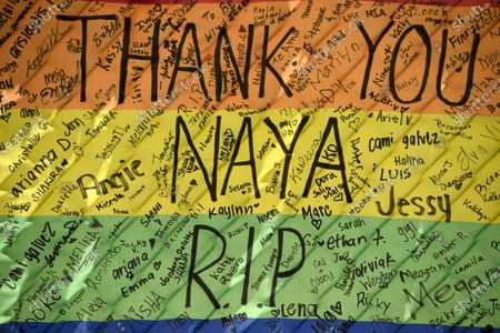 """The names of fans of the late actress Naya Rivera are written on a rainbow flag near Lake Piru, in Los Padres National Forest, Calif., about 55 miles (90 kilometers) northwest of Los Angeles. The 33-year-old Rivera, who played the lesbian cheerleader character Santana Lopez on the television series """"Glee,"""" was found dead in Lake Piru on July 13, five days after her son, Josey, was found alone on a boat the two had rented there"""