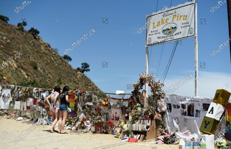"""Glee"""" fans Haley Deeds, left, and her sister Kaela, of Ventura, Calif., visit a makeshift memorial for the late """"Glee"""" cast member Naya Rivera at Lake Piru, in Los Padres National Forest, Calif., about 55 miles (90 kilometers) northwest of Los Angeles. The 33-year-old actress was found dead in Lake Piru on July 13, five days after her son, Josey, was found alone on a boat the two had rented there"""