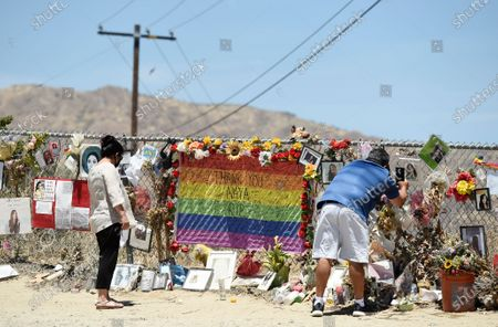 """Gerardo Lupercio, right, of Rosemont, Calif., and his wife Araceli visit a makeshift memorial for the late actress Naya Rivera at Lake Piru, in Los Padres National Forest, Calif., about 55 miles (90 kilometers) northwest of Los Angeles. The 33-year-old """"Glee"""" star was found dead in Lake Piru on July 13, five days after her son, Josey, was found alone on a boat the two had rented there"""