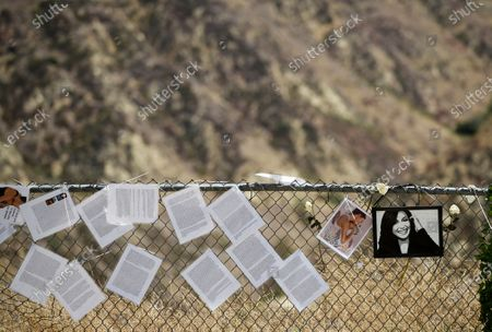 """Remembrances from fans sit alongside portraits of the late actress Naya Rivera on a fence at Lake Piru, in Los Padres National Forest, Calif., about 55 miles (90 kilometers) northwest of Los Angeles. The 33-year-old """"Glee"""" star was found dead in Lake Piru on July 13, five days after her son, Josey, was found alone on a boat the two had rented there"""