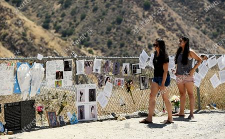 """Kaela Deeds, left, of Ventura, Calif. and her sister Haley visit a makeshift memorial for the late actress Naya Rivera at Lake Piru, in Los Padres National Forest, Calif., about 55 miles (90 kilometers) northwest of Los Angeles. The 33-year-old """"Glee"""" star was found dead in Lake Piru on July 13, five days after her son, Josey, was found alone on a boat the two had rented there"""