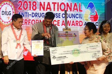 "Department of the Interior and Local Government (DILG) undersecretary for barangay affairs Martin Diño (center) with Special Assistant to the People (SAP) Christopher Lawrence ""Bong"" Tesoro Go (left) give the award to San Juan City Mayor Guia Guanzon Gomez (right) as one of the City in Metro Manila as drug free City during the 2018 National Anti-Drug Abuse Council Performance Awards at Manila Hotel in the City of Manila on December 28, 2018."