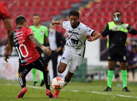 Stock Image of Luciano Acosta (L) of Atlas in action against Jeronimo Rodriguez (R) of Pumas UNAM during the Guard1anes 2020 Tournament soccer match between Atlas and Pumas UNAM at Jalisco Stadium in Guadalajara, Mexico, 03 August 2020.