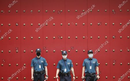 Police officers wearing face masks to help protect against the spread of the new coronavirus, stand guard in downtown Seoul, South Korea