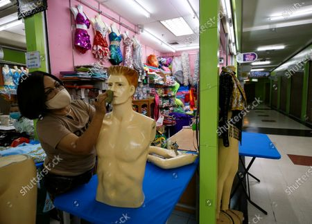 Stock Picture of Thai owner of a fancy fashion costume shop, Petchara Malalek polishes a mannequin as she waits for customers in a deserted wholesale clothes and accessories shopping mall otherwise busy with local and foreign shoppers, in Bangkok, Thailand, 04 August 2020. Petchara, a Thai owner of a fashion costumes shop said that her shop sales are down to zero causing her business to suffer as no foreign tourists, who are her main clients, are arriving to the country due to the COVID-19 pandemic. Thailand's Gross Domestic Product (GDP) is forecasted to shrink between 9.4 to 11.4 percent in 2020, the worst economic outlook in Asia caused by the global ongoing coronavirus disease (COVID-19) pandemic. The kingdom's economy would take two to three years for economic recovery.