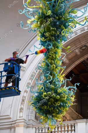 Stock Image of The V&A rotunda chandelier is cleaned ahead of the reopening of the museum on the 6th August after lockdown. The Ice Blue and Spring Green Chandelier by Dale Chihuly is only cleaned twice a year.