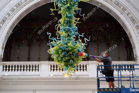 The V&A rotunda chandelier is cleaned ahead of the reopening of the museum on the 6th August after lockdown. The Ice Blue and Spring Green Chandelier by Dale Chihuly is only cleaned twice a year.