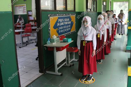 A number of students wearing masks and face shields lined up in front of the class before entering the classroom to take part in face-to-face learning at State Elementary School 06. The Bekasi City Government has given permission to six pilot schools in its area to conduct one-month face-to-face learning trials.