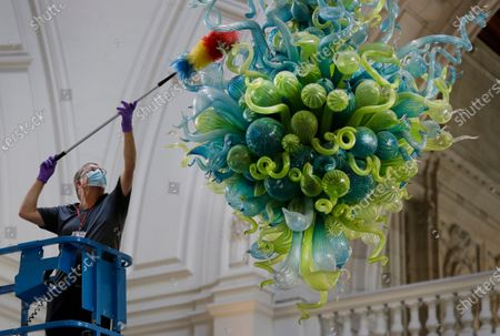23:01 GMT ) . A museum technician cleans one of the V&A's most iconic and largest objects: a 27-foot glass chandelier made up of 1,300 exquisite blue and green glass elements, that hangs in the museum's Grand Entrance at the in London, Tuesday, Aug. 4, 2020. The chandelier is the V&A Rotunda Chandelier by Dale Chihuly, 2001. On loan from Chihuly Studio, Seattle, Washington, USA. The museum will reopen to the public on Thursday Aug.6