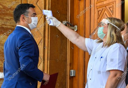 A health worker checks the temperature of the former Foreign Minister and new lawmaker Nikola Dimitrov (L) at the entrance of the parliament building prior to the start of the constitutive session in Skopje, Republic of North Macedonia, 04 August 2020. North Macedonia's parliament held the constitutive session where the mandates of all 120 lawmakers have been verified which have been elected on the early parliamentary elections on 15 July 2020. Political negotiations are expected of the main political parties in the country, SDSM (46 lawmakers) and VRMO DPMNE (44 lawmakers), with the Albanian political parties in the fight for the majority of the 120 parliament members. The constitutive session was held under strict measures because of the pandemic COVID-19.