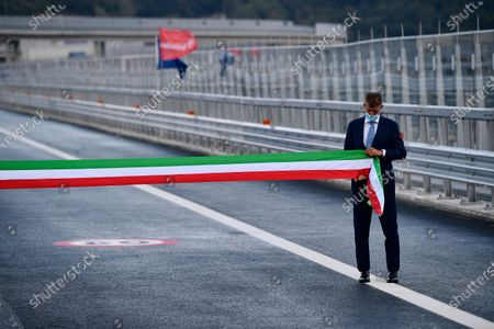 A man holds an Italian tricolor ribbon during the official inauguration ceremony of the new San Giorgio bridge. The new San Giorgio bridge designed by architect Renzo Piano replaces Morandi bridge that collapsed in August 2018 and the new bridge is set to reopen on 05 August 2020 during the inauguration ceremony.