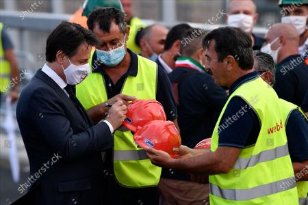 Italian Prime Minister Giuseppe Conte wearing a facemask signs the protective cap of the workers at the construction site during the official inauguration ceremony of the new San Giorgio bridge. The new San Giorgio bridge designed by architect Renzo Piano replaces Morandi bridge that collapsed in August 2018 and the new bridge is set to reopen on 05 August 2020 during the inauguration ceremony.