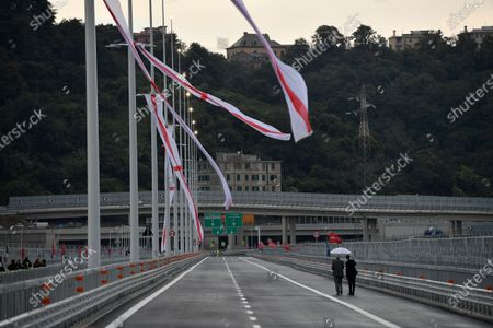 Renzo Piano walks with his assistant holding an umbrella on the new San Giorgio bridge he designed before the official inauguration ceremony. The new San Giorgio bridge designed by architect Renzo Piano replaces Morandi bridge that collapsed in August 2018 and the new bridge is set to reopen on 05 August 2020 during the inauguration ceremony.