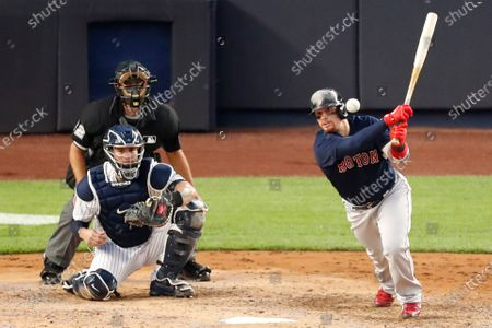 Stock Picture of Boston Red Sox center designated hitter Christian Vazquez bats in a baseball game against the New York Yankees, at Yankee Stadium in New York. Home plate umpire James Hoye watches the play along with New York Yankees catcher Gary Sanchez