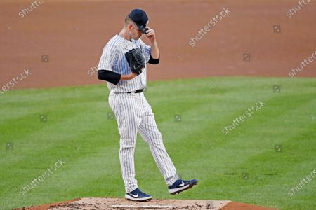 New York Yankees starting pitcher James Paxton reacts after allowing a double to Boston Red Sox's J.D. Martinez during the first inning of a baseball game, at Yankee Stadium in New York