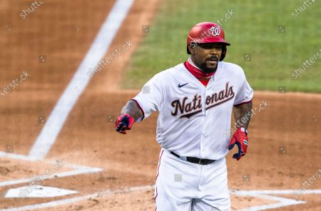 Washington Nationals Howie Kendrick gestures after scoring on his home run during the first inning of the team's baseball game against the New York Mets in Washington