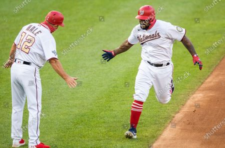 Washington Nationals Howie Kendrick, right, rounds the bases after hitting a home run during the first inning of a baseball game against the New York Mets in Washington