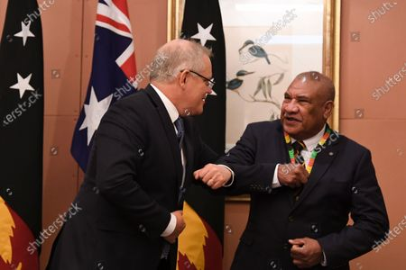 Australian Prime Minister Scott Morrison (L) and PNG High Commissioner to Australia John Kali (R) bump elbows at a signing ceremony with Prime Minister of Papua New Guinea James Marape during a virtual summit on health, investment and security at Parliament House in Canberra, Australia, 05 August 2020.