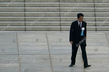 Japanese Prime Minister Shinzo Abe walks off after delivering a speech during a ceremony to mark the 75th anniversary of the bombing at the Hiroshima Peace Memorial Park, in Hiroshima, western Japan