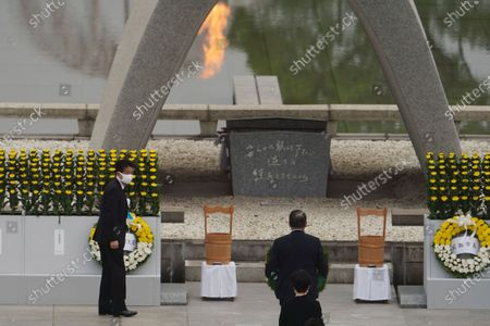 Japanese Prime Minister Shinzo Abe offers flowers to Hiroshima Memorial Cenotaph during a ceremony to mark the 75th anniversary of the bombing at the Hiroshima Peace Memorial Park, in Hiroshima, western Japan