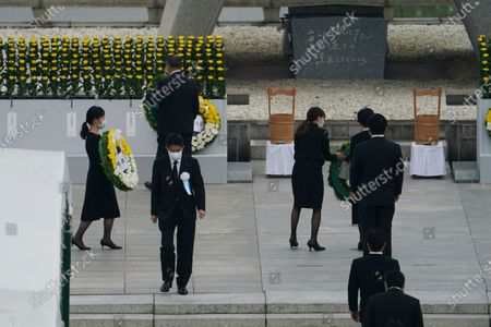 Japanese Prime Minister Shinzo Abe walks off after offering flowers to Hiroshima Memorial Cenotaph during a ceremony to mark the 75th anniversary of the bombing at the Hiroshima Peace Memorial Park, in Hiroshima, western Japan