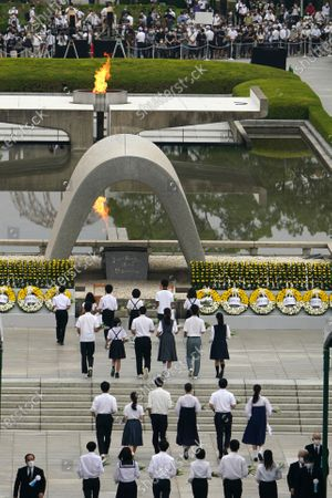 The family of the deceased offer flowers to Hiroshima Memorial Cenotaph during the ceremony to mark the 75th anniversary of the bombing at the Hiroshima Peace Memorial Park, in Hiroshima, western Japan