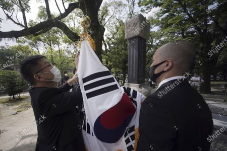 Staff members adjust a South Korean flag by the Monument to Korean Victims and Survivors, the cenotaph for Korean atomic bomb victims, at Hiroshima Peace Memorial Park in Hiroshima, western Japan, . Hiroshima marks the 75th anniversary of the world's first atomic bombing on Aug. 6