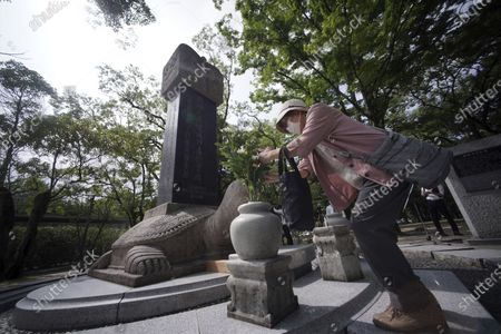 Woman offers flowers and prays before a memorial service for Korean atomic bomb victims in front of Monument to Korean Victims and Survivors at Hiroshima Peace Memorial Park in Hiroshima, western Japan, . Hiroshima marks the 75th anniversary of the world's first atomic bombing on Aug. 6