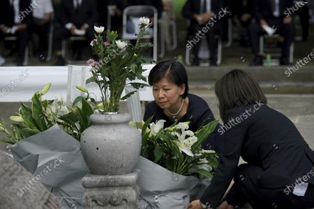 Izumi Nakamitsu, U.N. undersecretary-general and high representative for disarmament affairs, offers flower as South Korean residents living in Japan gather for a memorial service in front of the cenotaph for Korean atomic bomb victims at Hiroshima Peace Memorial Park in Hiroshima, western Japan, . Hiroshima marks the 75th anniversary of the world's first atomic bombing on Aug. 6