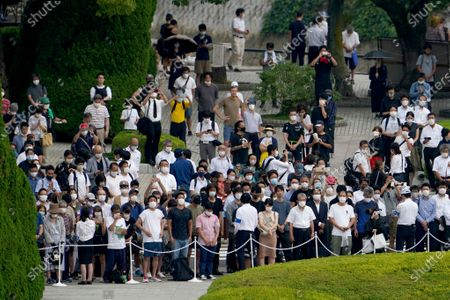 Visitors observe a minute of silence for the victims of the atomic bombing, at 8:15am, the time atomic bomb exploded over the city, at the Hiroshima Peace Memorial Park during the ceremony to mark the 75th anniversary of the bombing, in Hiroshima, western Japan