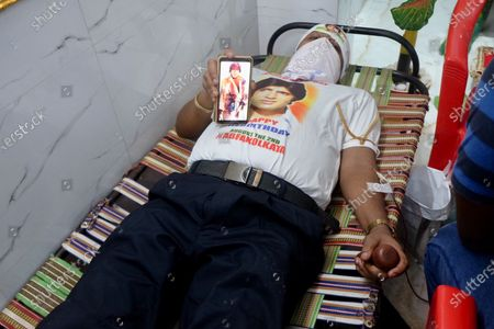 A fan is donating blood on World Fans Day at Amitabh Bachchan Temple as they celebrate second birthday anniversary of  Bollywood actor Amitabh Bachchan as they expect him to be  release  from the hospital after fighting with Covid -19.