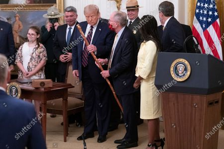 United States Senator Lamar Alexander (Republican of Tennessee) hands a walking stick to United States President Donald J. Trump during a signing ceremony for H.R. 1957 - The Great American Outdoors Act in the East Room of the White House in Washington, DC. Looking on at left is US Senator Cory Gardner (Republican of Colorado).