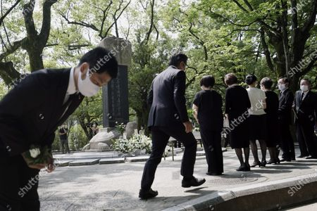 Guests pray during a memorial service for Korean atomic bomb victims in front of Monument to Korean Victims and Survivors at Hiroshima Peace Memorial Park in Hiroshima, western Japan, . Hiroshima marks the 75th anniversary of the world's first atomic bombing on Aug. 6