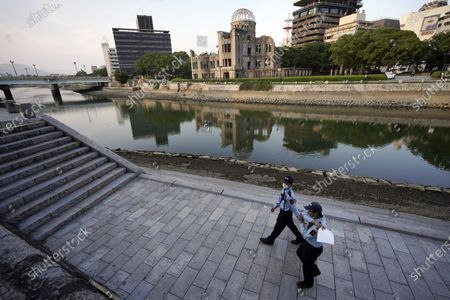 Security guards patrol near the Atomic Bomb Dome in Hiroshima, western Japan, . The city of Hiroshima on Thursday, Aug. 6, marks the 75th anniversary of the U.S. atomic bombing