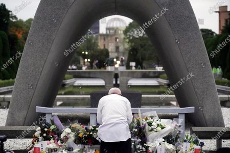 Man prays in front of the cenotaph for the atomic bombing victims before the start of ceremony to mark the 75th anniversary of the bombing in Hiroshima, western Japan, early