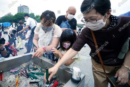 People burn joss sticks in front of the cenotaph for the atomic bombing victims before the start of a ceremony to mark the 75th anniversary of the U.S. bombing in Hiroshima, western Japan, early