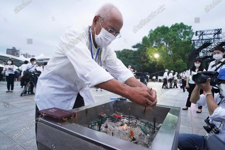 Visitor burns joss sticks in front of the cenotaph for the atomic bombing victims before the start of a ceremony to mark the 75th anniversary of the U.S. bombing in Hiroshima, western Japan, early