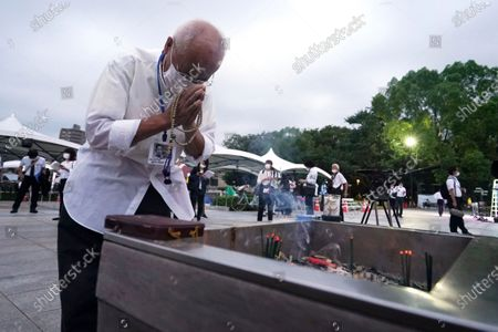 Visitor prays in front of the cenotaph for the atomic bombing victims before the start of a ceremony to mark the 75th anniversary of the U.S. bombing in Hiroshima, western Japan, early