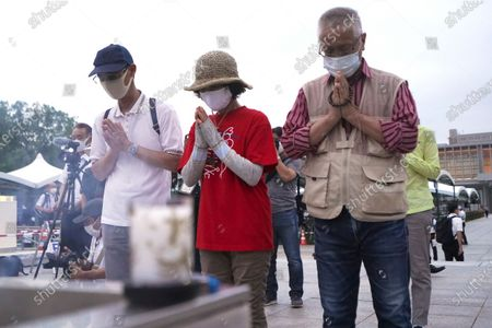 People pray in front of the cenotaph for the atomic bombing victims before the start of a ceremony to mark the 75th anniversary of the U.S. bombing in Hiroshima, western Japan, early