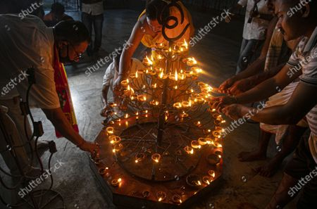 Hindus light earthen lamps and perform special prayers to mark the groundbreaking ceremony of a temple dedicated to the Hindu god Ram in Ayodhya, in a temple in Gauhati, India, . Despite the coronavirus restricting a large crowd, Hindus rejoiced as Indian Prime Minister Narendra Modi broke ground Wednesday on a long-awaited temple of their most revered god Ram at the site of a demolished 16th century mosque