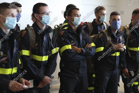 Members of the Securite Civile rescue organisation wait in line before boarding a plane at Charles de Gaulle airport, north of Paris, Wednesday, Aug.5, 2020. France is sending two planes to Lebanon on Wednesday with dozens of emergency workers, a mobile medical unit and 15 tons of aid. The aid is expected to arrive Wednesday afternoon and should allow for the treatment of some 500 blast victims, according to French President Emmanuel Macron's office