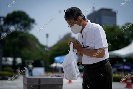 A man wearing a protective face mask prays in front of a cenotaph at Peace Memorial Park in Hiroshima, Japan, 05 August 2020. On 06 August 2020 Japan will mark the 75th anniversary of the bombing of Hiroshima. In 1945 the United States dropped two nuclear bombs over the cities of Hiroshima and Nagasaki on 06 and 09 August respectively, killing more than 200,000 people. This year's annual commemoration events were either canceled or scaled down amid the ongoing coronavirus pandemic.