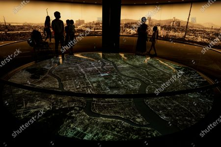 Visitors look at a projection showing the map of Hiroshima, at the Hiroshima Peace Memorial Museum in Hiroshima, Japan, 05 August 2020. On 06 August 2020 Japan will mark the 75th anniversary of the bombing of Hiroshima. In 1945 the United States dropped two nuclear bombs over the cities of Hiroshima and Nagasaki on 06 and 09 August respectively, killing more than 200,000 people. This year's annual commemoration events were either canceled or scaled down amid the ongoing coronavirus pandemic.