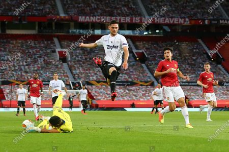 Husein Balic of LASK jumps over a rushing Sergio Romero of Manchester United