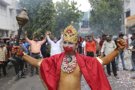 Man dressed as Hindu god Hanuman participates in a celebration by Vishwa Hindu Parishad or World Hindu Council to mark the groundbreaking ceremony of a temple dedicated to Hindu god Ram in Ayodhya, in Ahmedabad, India, . Despite the coronavirus restricting a large crowd, Hindus rejoiced as Indian Prime Minister Narendra Modi broke ground Wednesday on a long-awaited temple of their most revered god Ram at the site of a demolished 16th century mosque