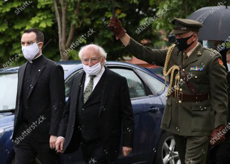 The President of Ireland Michael D Higgins, center, arrives to attend former Northern Ireland lawmaker and Nobel Peace Prize winner John Hume's funeral Mass at St Eugene's Cathedral in Londonderry, Northern Ireland, . Hume was co-recipient of the 1998 Nobel Peace Prize with fellow Northern Ireland lawmaker David Trimble, for his work in the Peace Process in Northern Ireland. Higgins is wearing a mask due ti the ongoing outbreak of the Coronavirus
