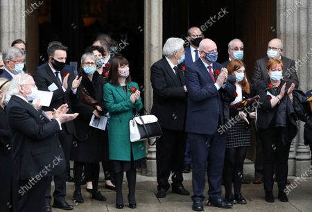 Mourners including the President of Ireland Michael D. Higgins, left, applaud as the funeral cortege of the the former Northern Ireland lawmaker and Nobel Peace Prize winner John Hume leaves following the funeral Mass at St Eugene's Cathedral in Londonderry, Northern Ireland, . Hume was co-recipient of the 1998 Nobel Peace Prize with fellow Northern Ireland lawmaker David Trimble, for his work in the Peace Process in Northern Ireland. Masks are worn due to the ongoing Coronavirus outbreak