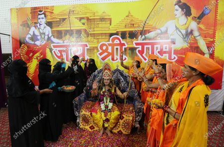 Stock Photo of A man dressed as Lord Rama (C) is showered with flowers by Hindu devotees as they celebrate the laying of the foundation stone of the Rama temple in Ayodhya, in Bhopal, India, 05 August 2020. Indian Prime Minister Narendra Modi laid the foundation stone of the Rama Temple in Ayodhya, Uttar Pradesh, on 05 August, months after India's Supreme Court ruled that the site should be given to Hindus after a dispute concerning the control of the area, regarded as the birthplace of Lord Rama. The site had previously hosted the Babri Masjid, a mosque destroyed by Hindu nationalists in 1992. The courts also ruled that Muslim devotees would be assigned a separate lot to rebuild the mosque.